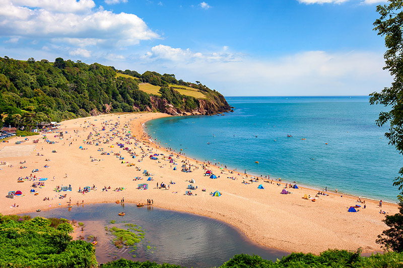 A sunny seascape with people enjoying the beach in Blackpool Sands, Devon.