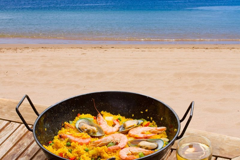 Paella and a glass of wine by the beach - a Valencian classic!