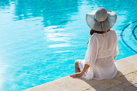 Woman with hat on by a swimming pool